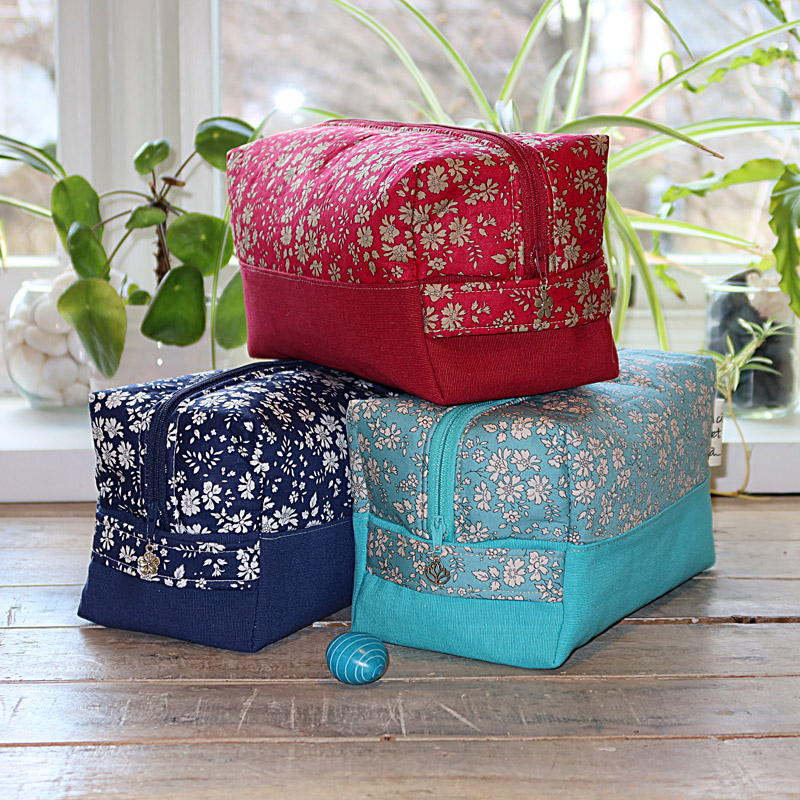 three handmade liberty toiletry bags, navy, red, and turquoise